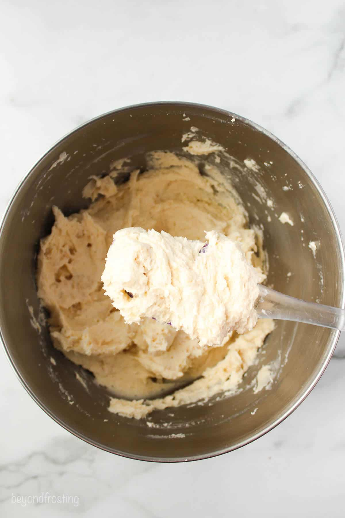 a spatula with frosting being held over a metal mixing bowl