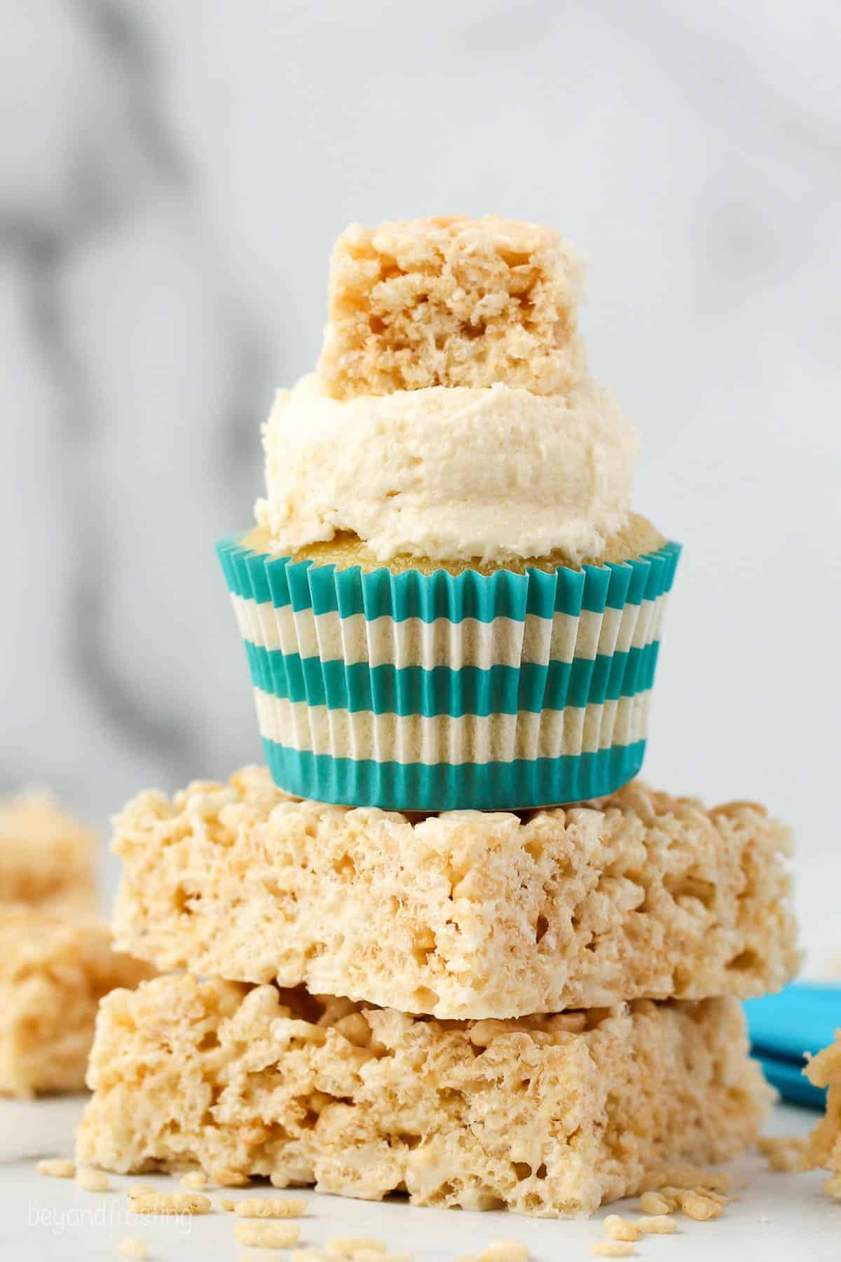 Two rice krispie treats stacked, with a cupcake on top garnished with a mini rice krispie treat