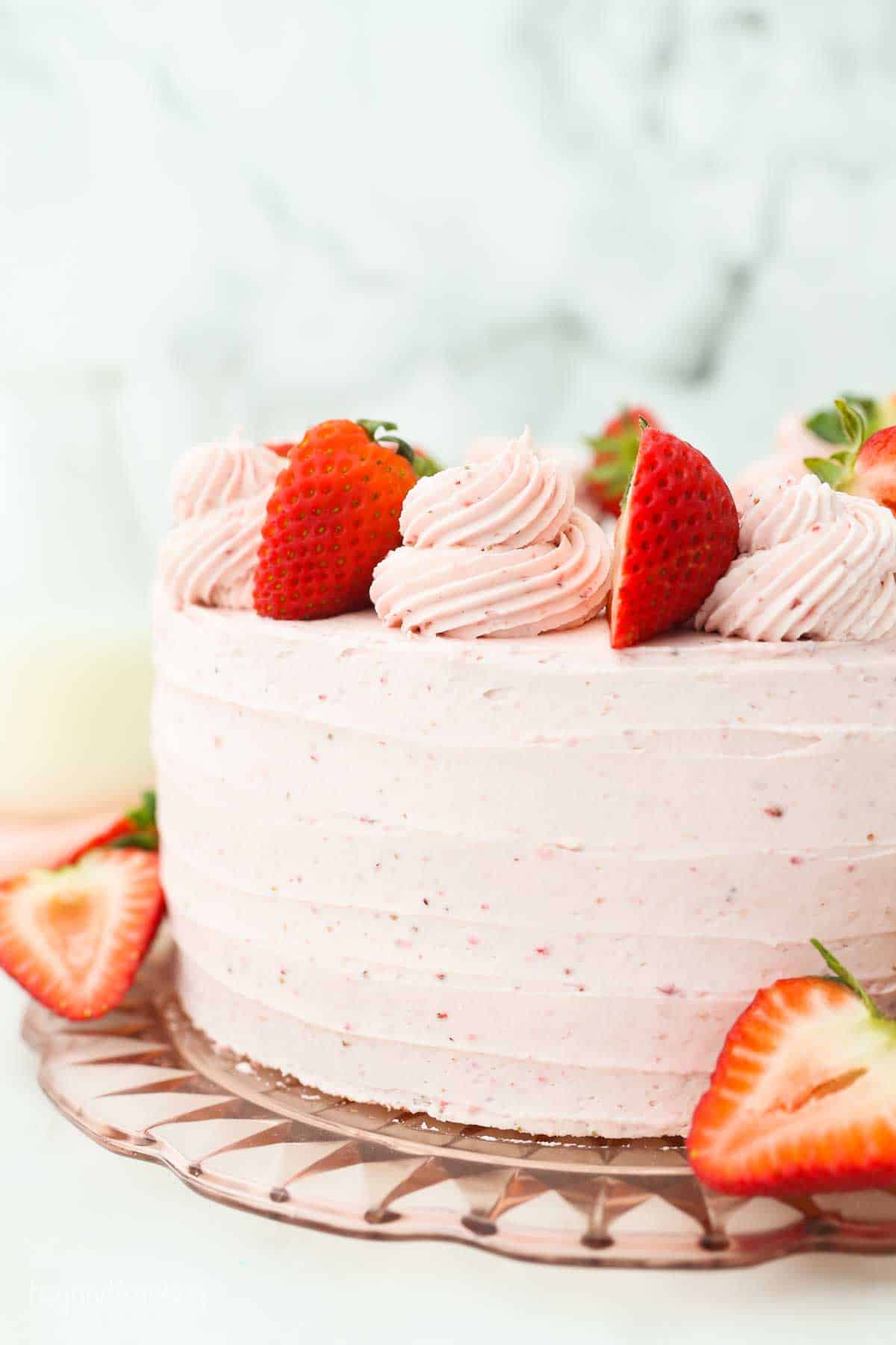 A fully decorated Strawberry Cake with Strawberry frosting, garnished with fresh strawberries.