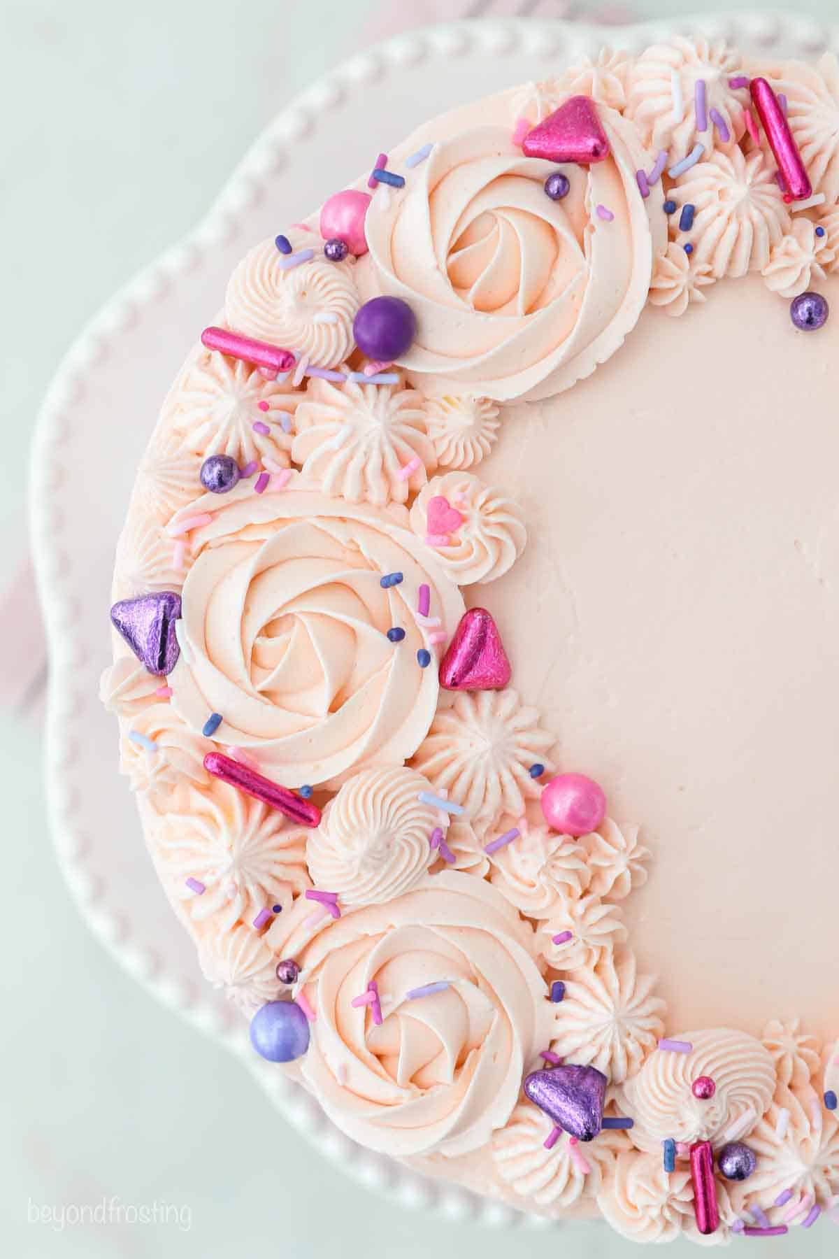 The top of a the cake, decorated with frosting roses and sprinkles.