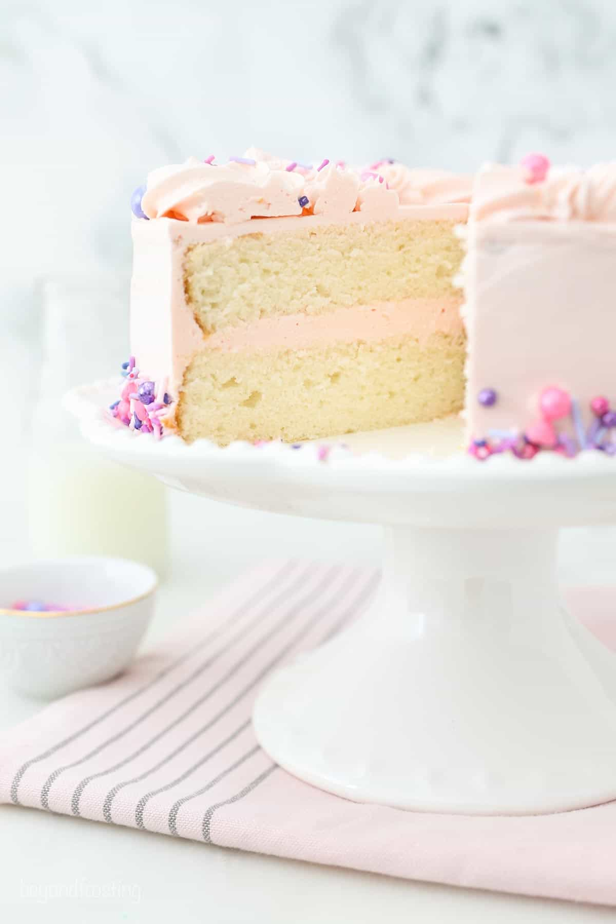 A White Cake with a slice taken out, showing the two layers with the frosting in between.