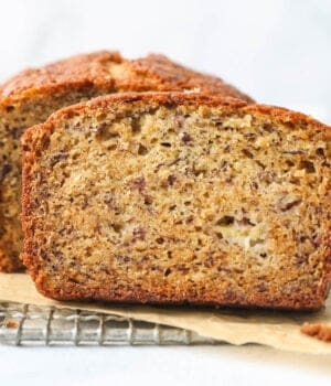 a close up of a slice of banana bread on a wire rack
