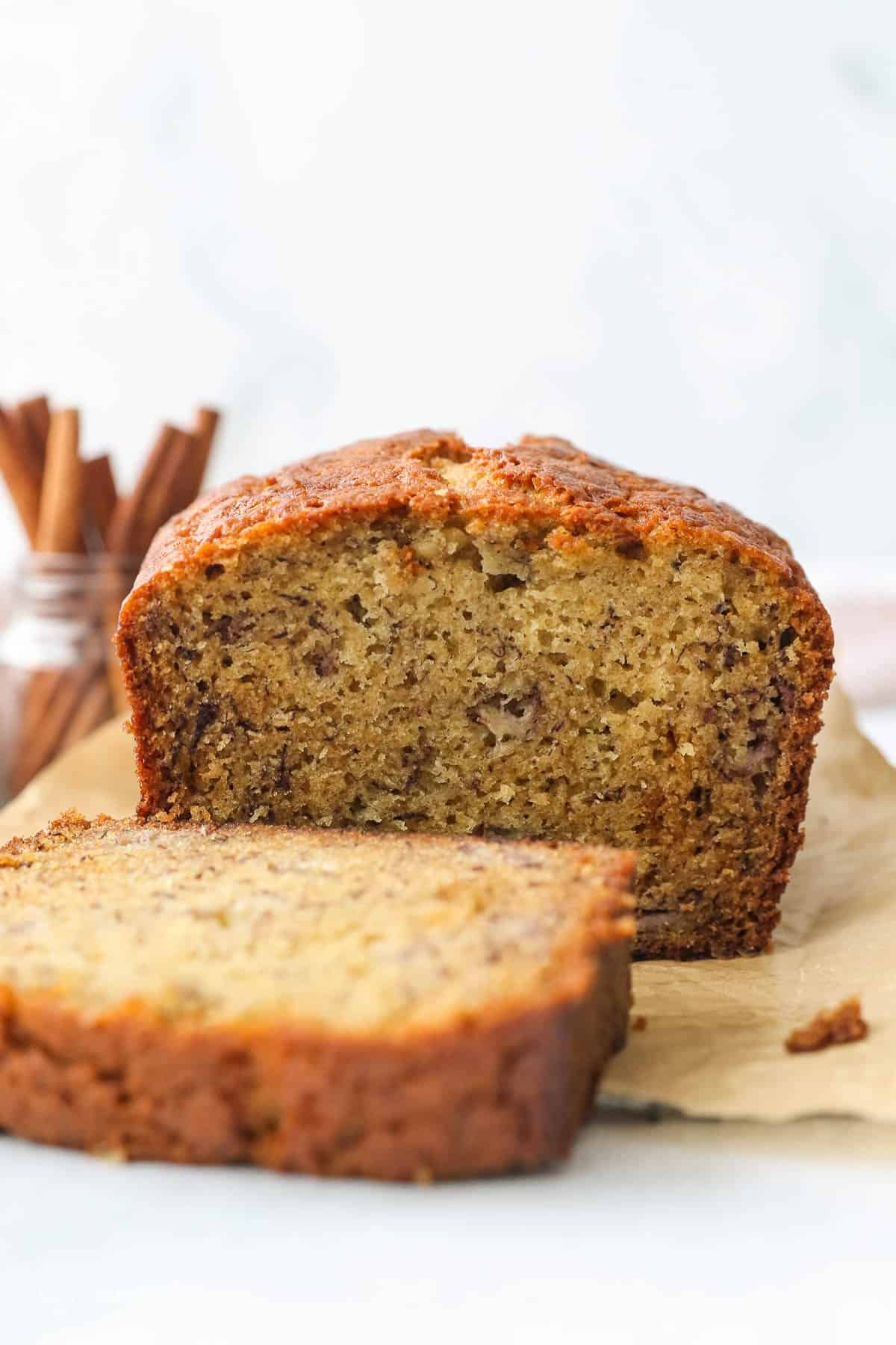 A loaf of banana bread with a slice cut off.