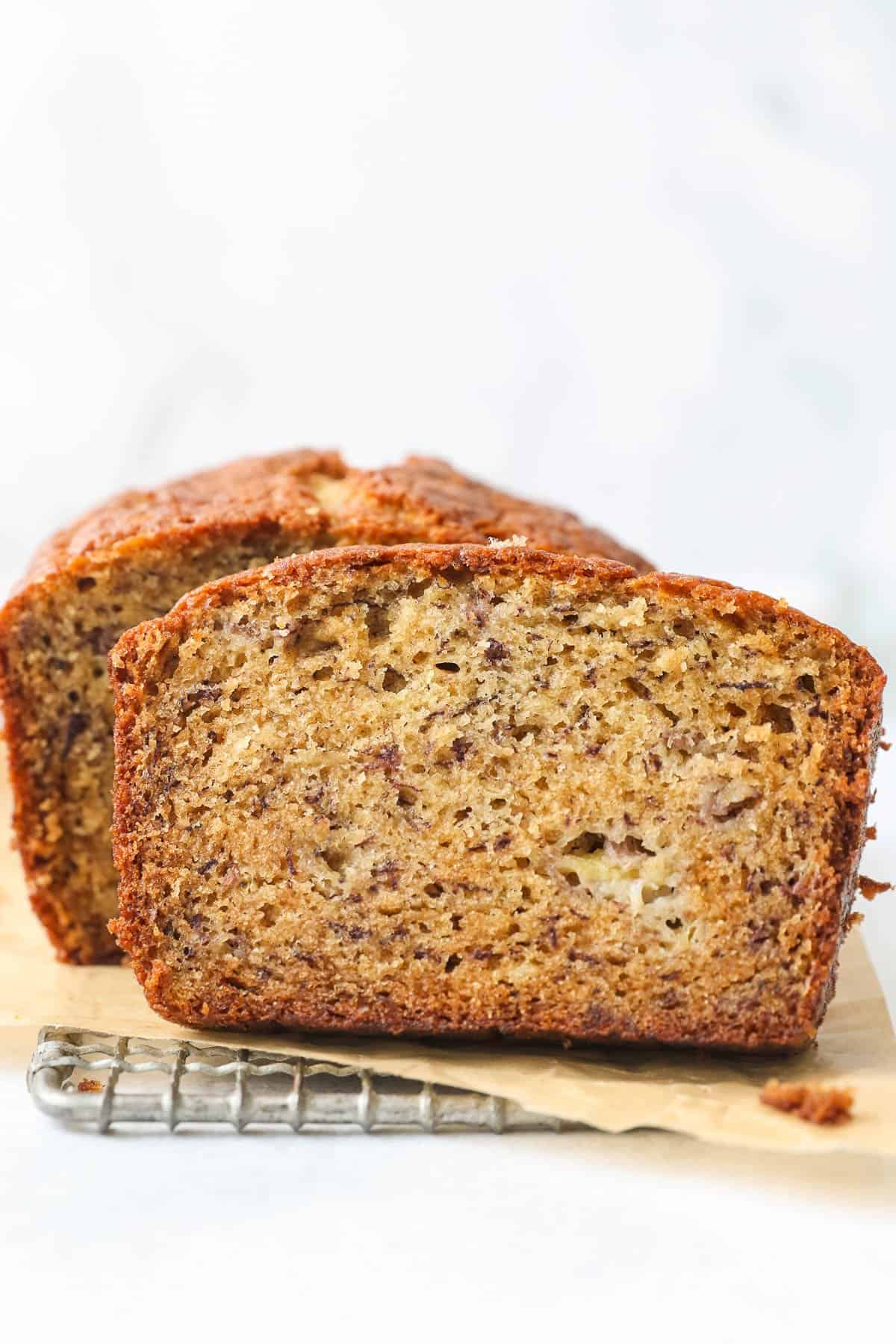 A slice of banana bread in front of a full loaf.
