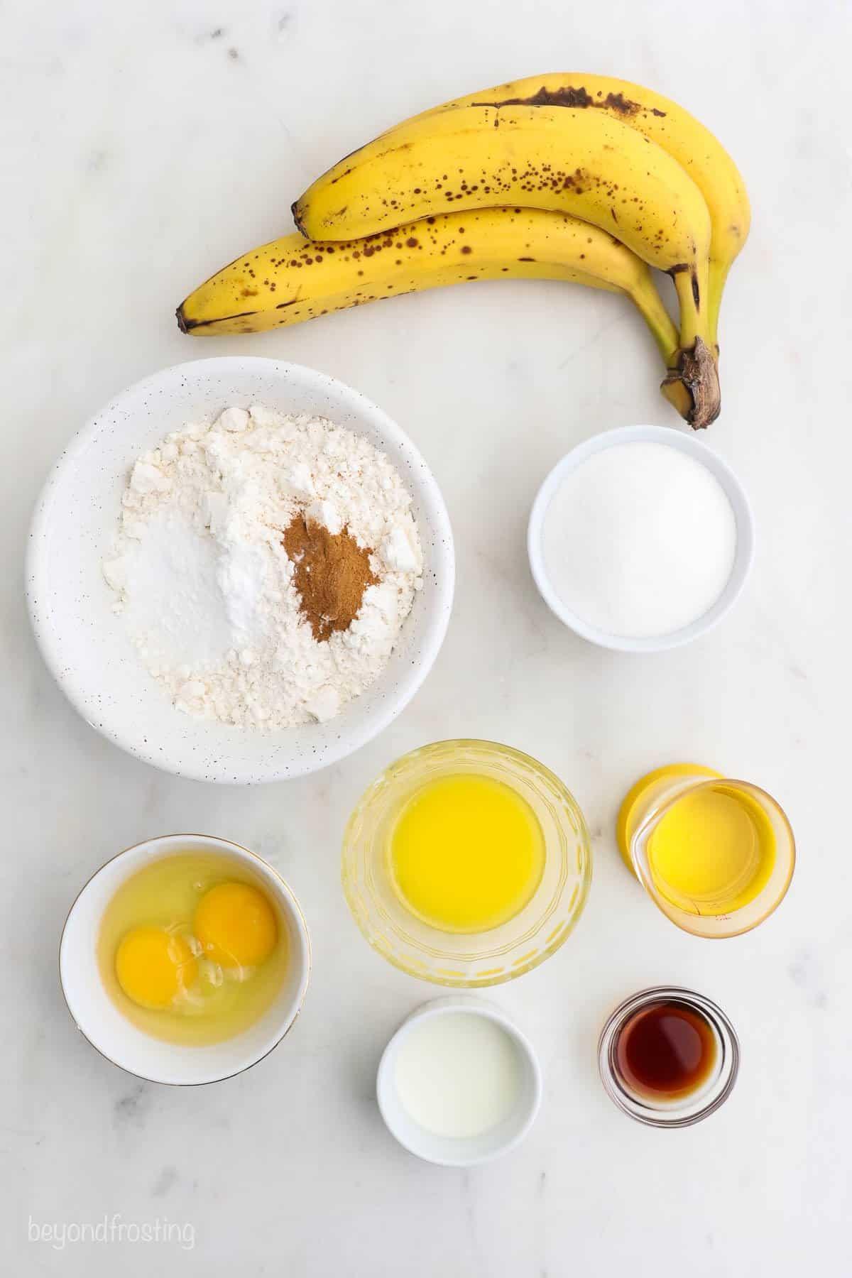 All of the ingredients for banana bread: baking soda, baking powder, salt, vanilla, cinnamon, bananas, sugar, flour, oil, eggs, and milk.