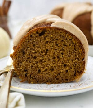 a white plate with a slice of pumpkin cake and two gold forks