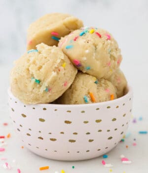 a close up of a pink bowl filled with scoops of sugar cookie dough