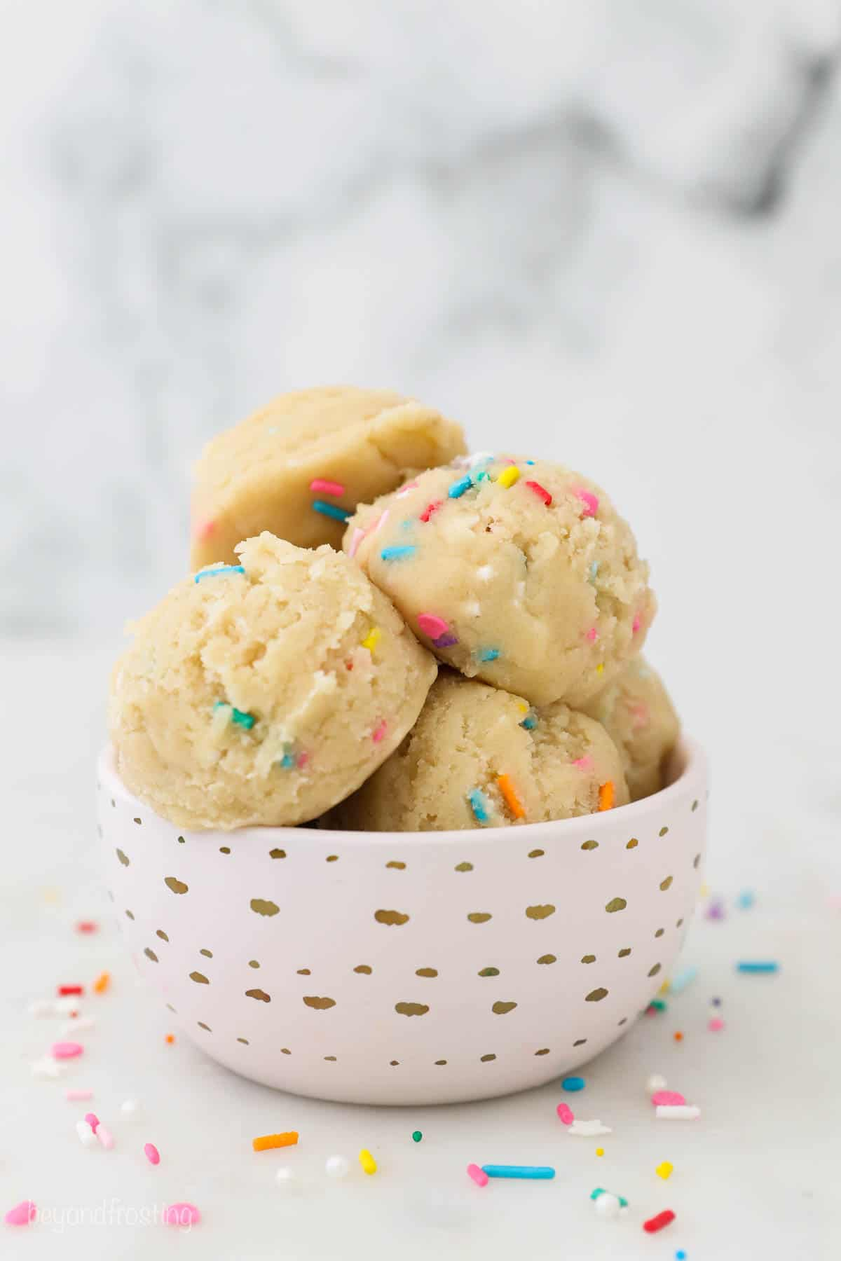 A pink bowl with gold dots filled with scooped of cookie dough with sprinkles