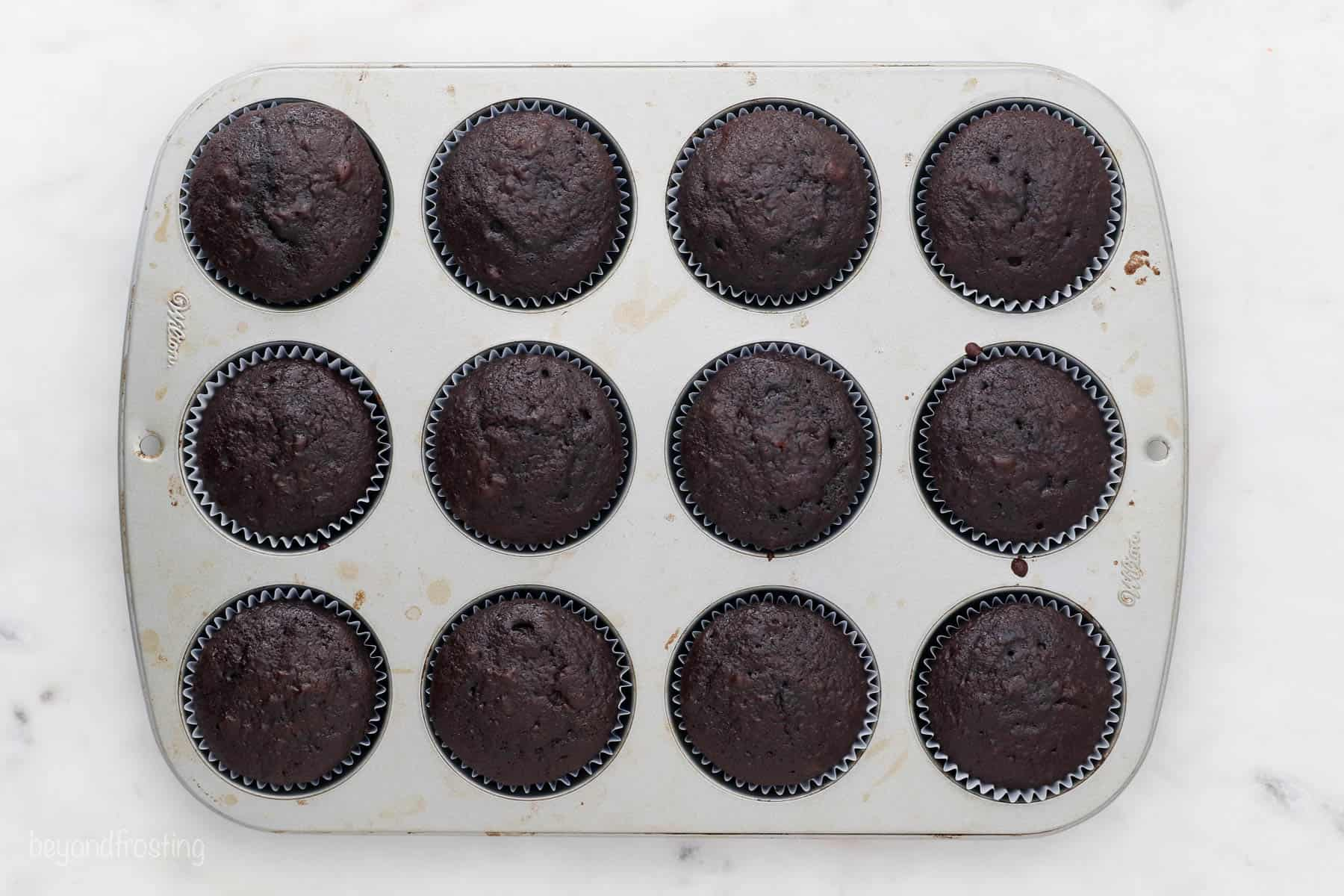 overhead of cupcake pan with baked chocolate cupcakes