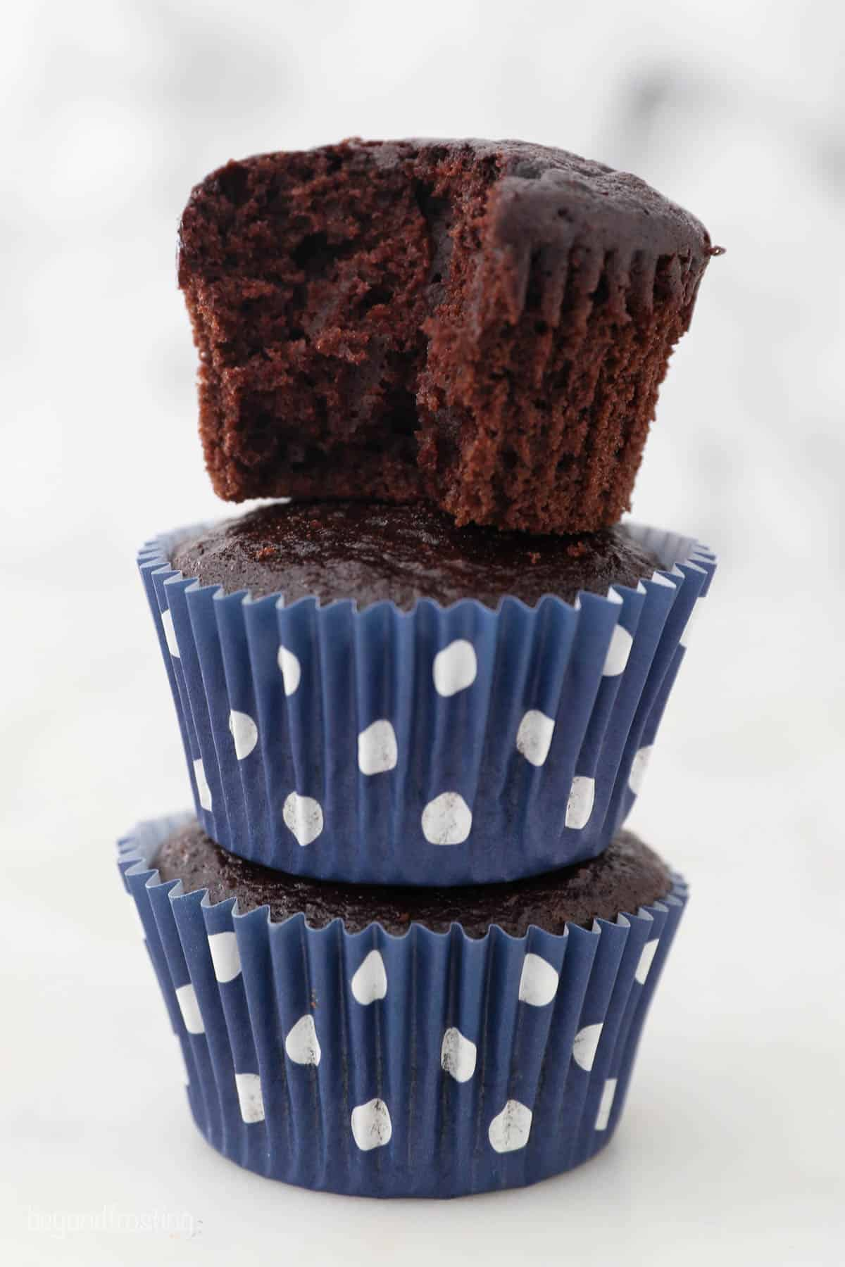 3 stacked chocolate cupcakes, the top one is unwrapped with a bite removed