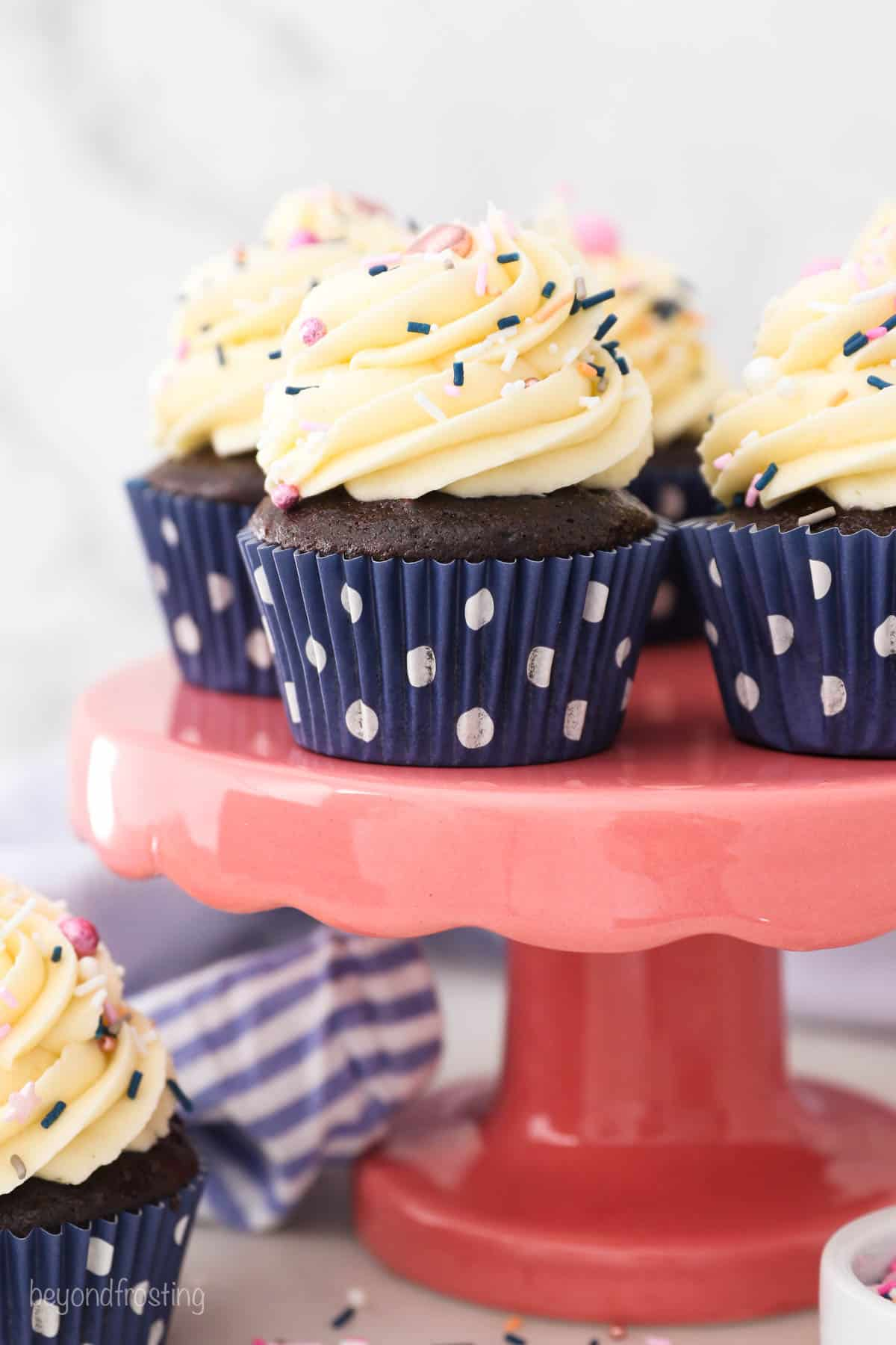 A pink cake stand with chocolate frosted cupcakes in navy blue polka dot wrappers