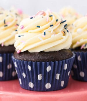 a close up of a chocolate cupcake with vanilla frosting and sprinkles
