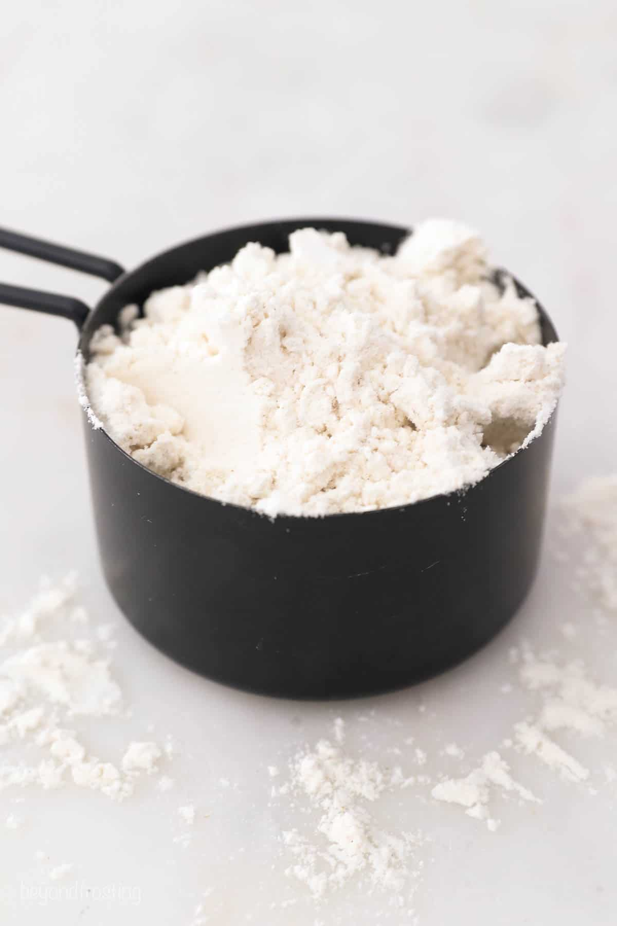 a black measuring cup with flour