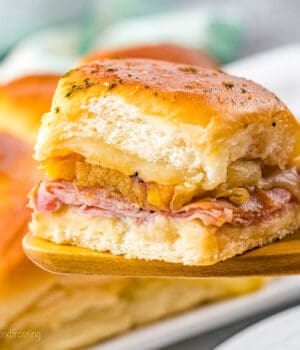 A close up of a ham and cheese slider on a wooden spoon