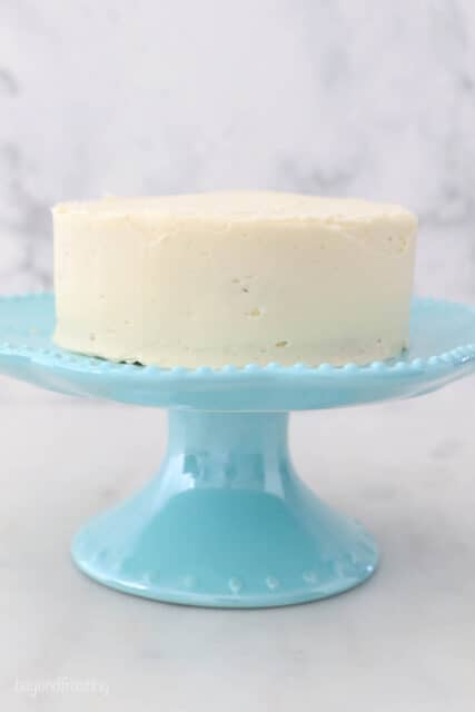 a small frosted cake on a teal cake stand