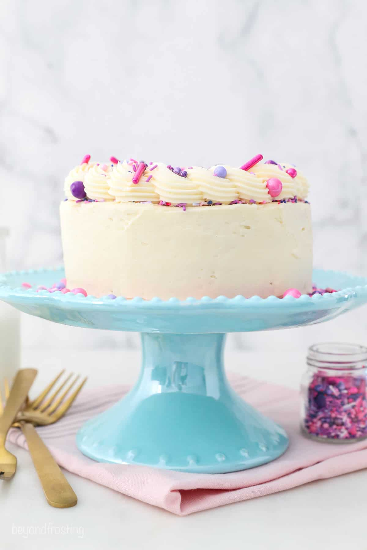 a decorated vanilla cake on a teal cake stand, pink napkin and gold forks