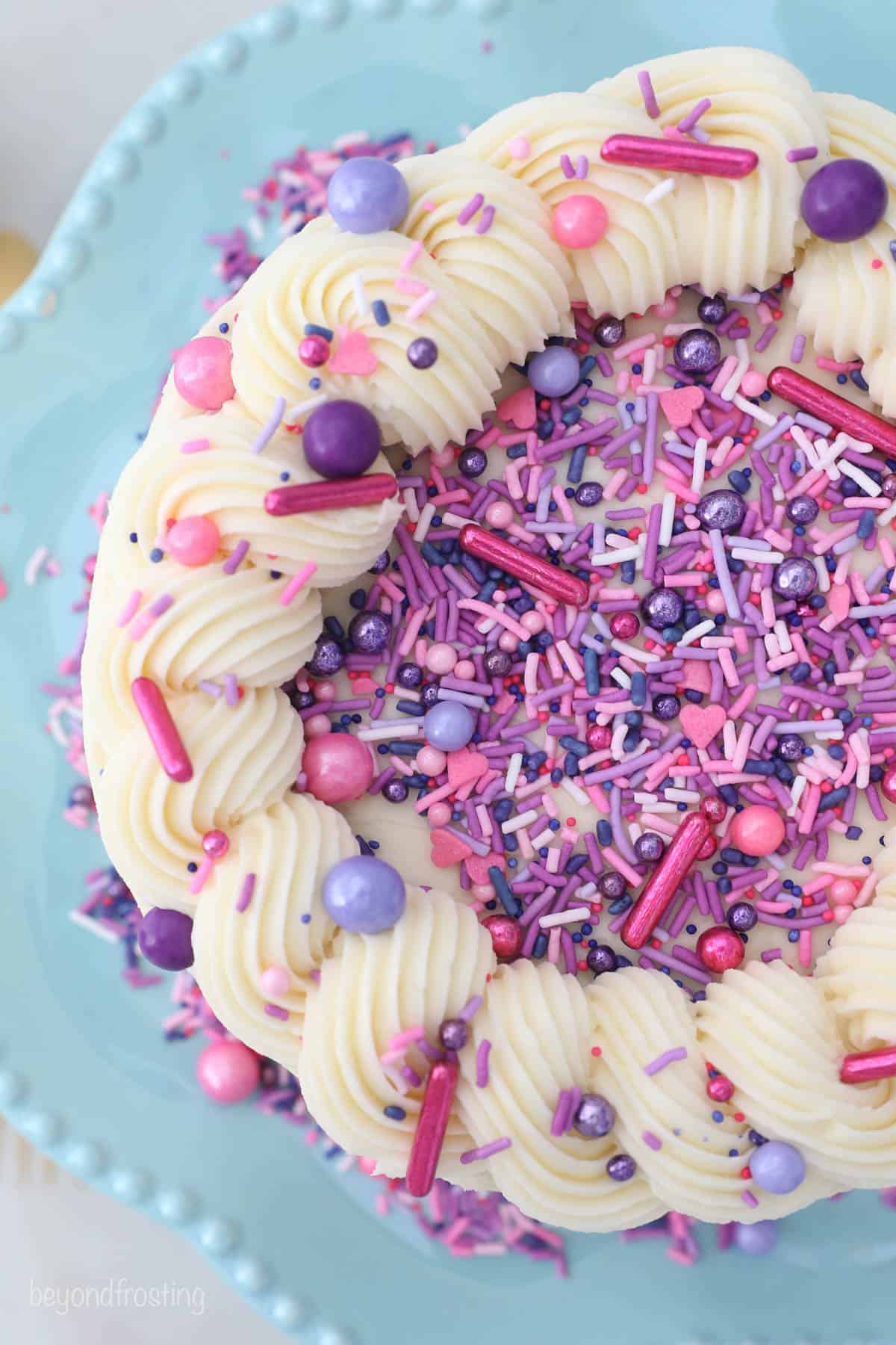overhead view of a decorated cake with pink and purple sprinkles
