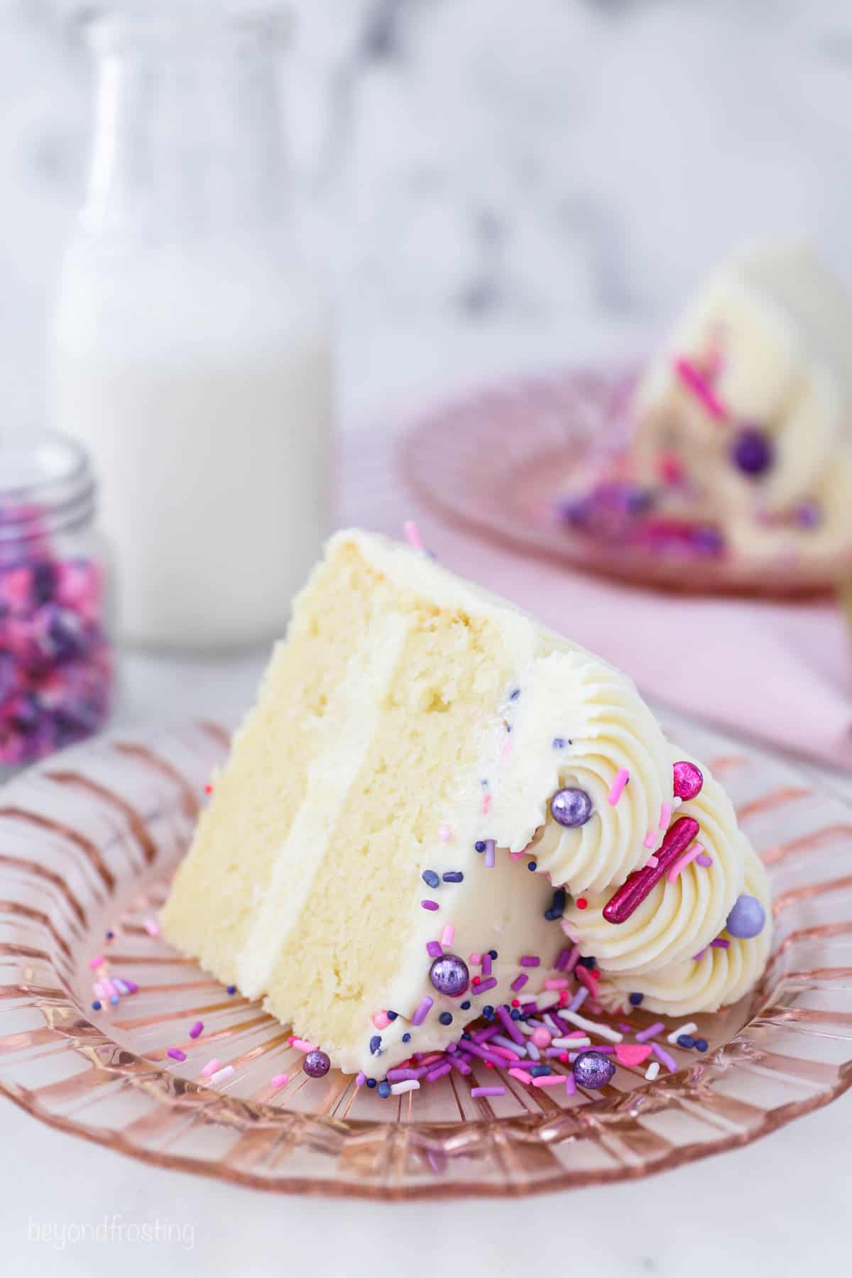 a small slice of vanilla cake with pink and purple sprinkles on a pink glass plate