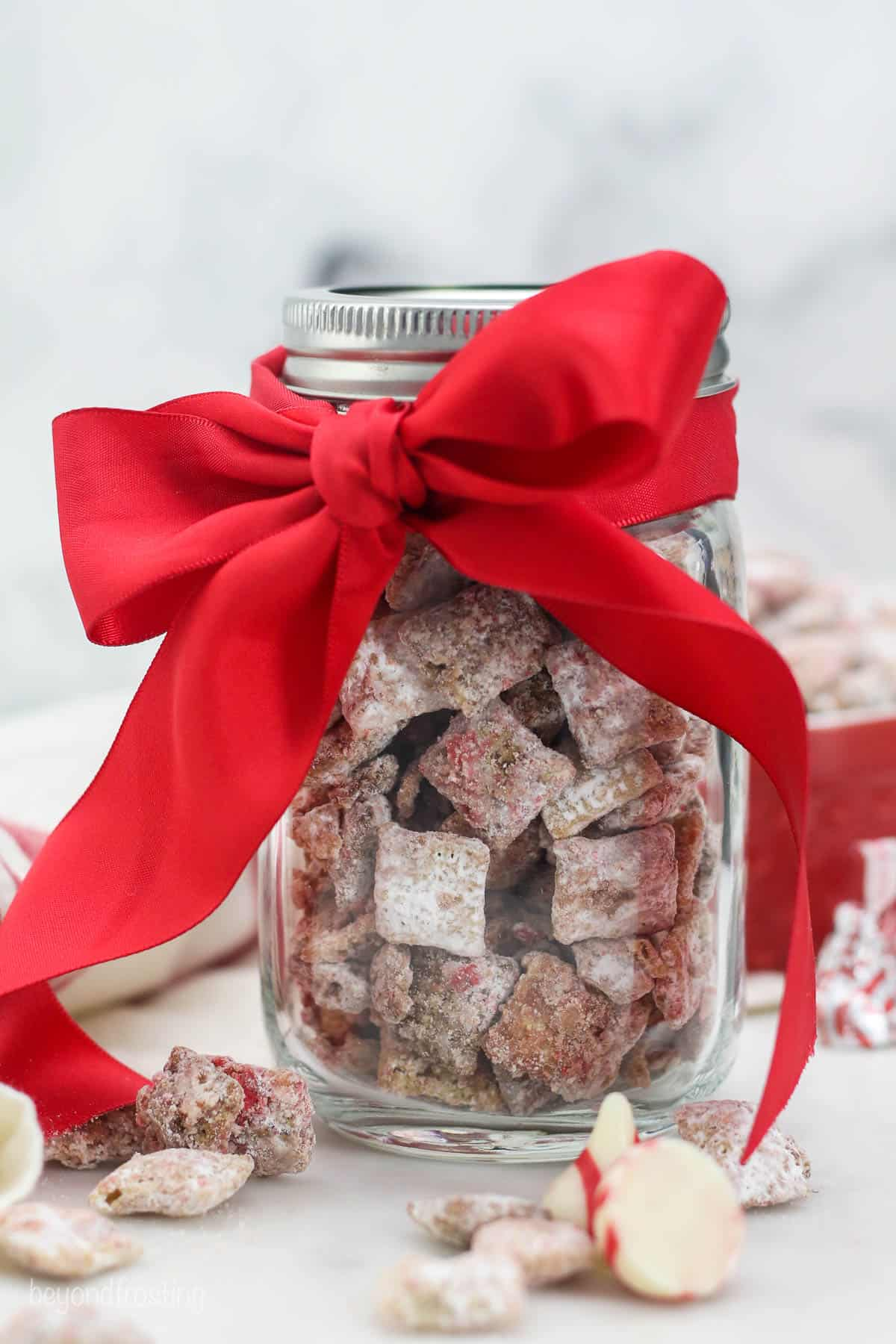 mason jar with peppermint puppy chow tied with a bow
