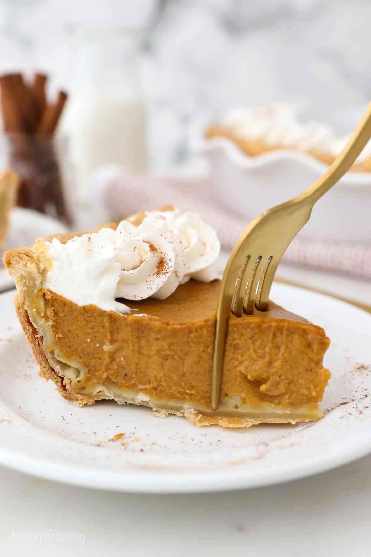 A fork cutting into a slice of Pumpkin Pie with Homemade Whipped Cream.