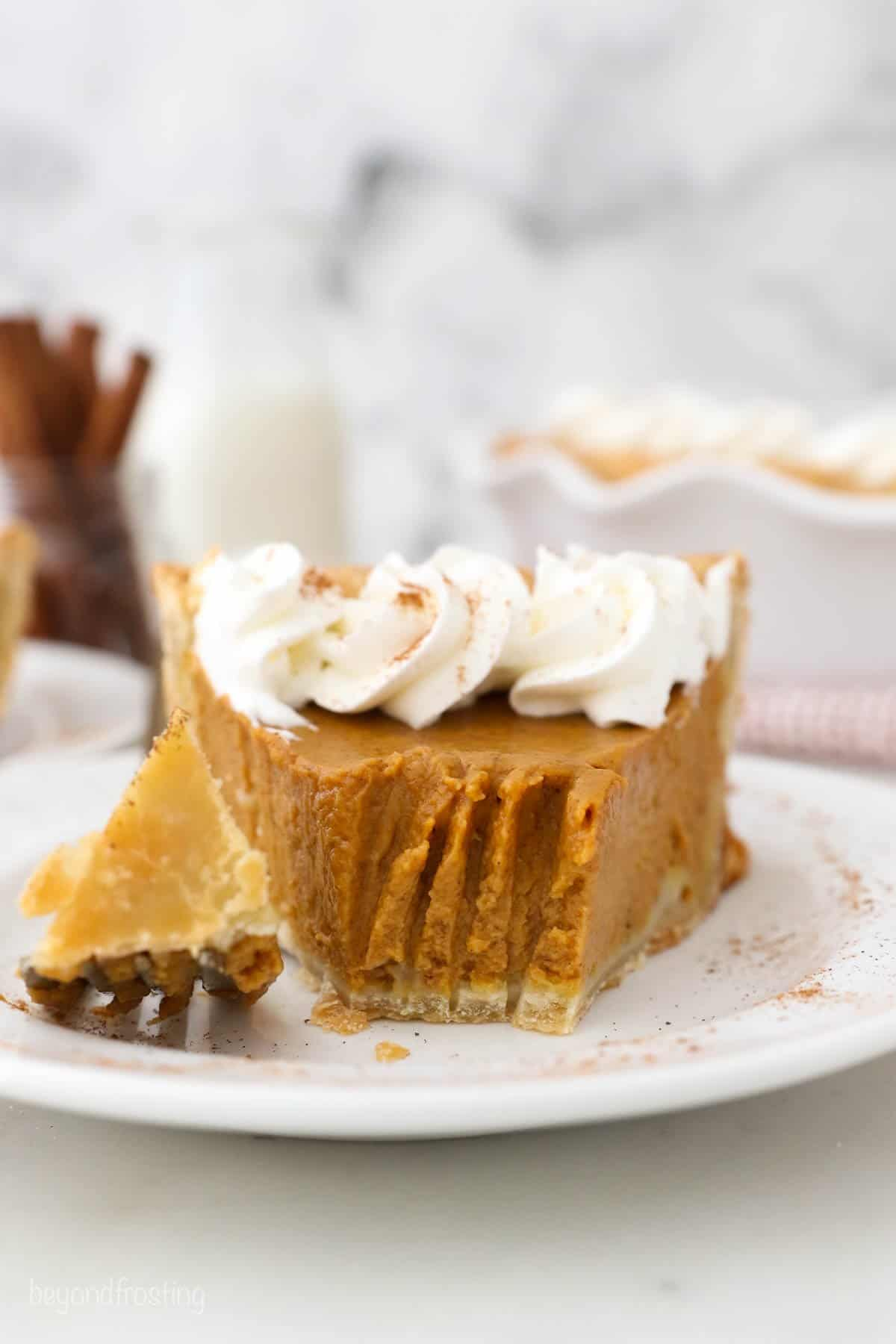 A slice of Pumpkin Pie with Homemade Whipped Cream with a piece taken out from a fork.