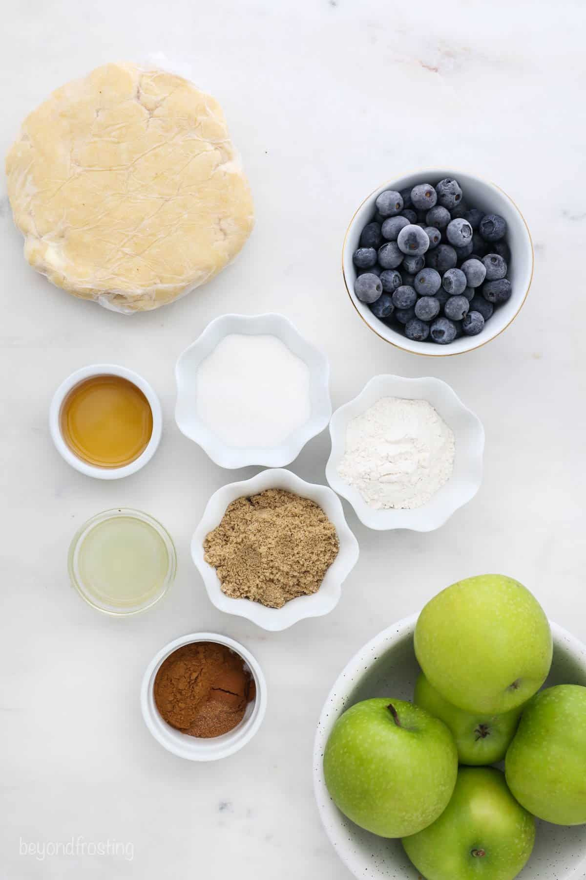 Ingredients for an apple pie laid out o a table