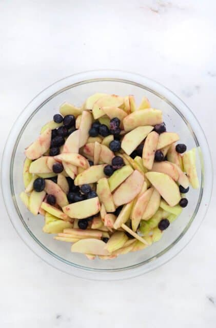 a glass bowl with sliced apples and blueberries