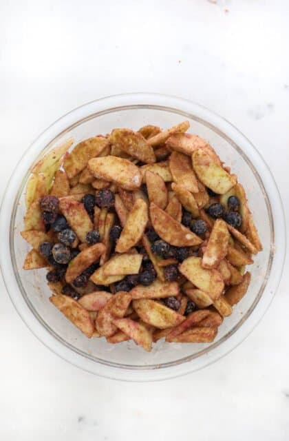 a glass bowl with sliced apples and blueberries tossed in cinnamon and sugar