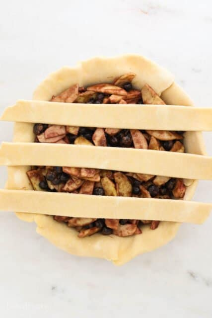 a pie plate filling with pie filling and 3 strips of dough laying across