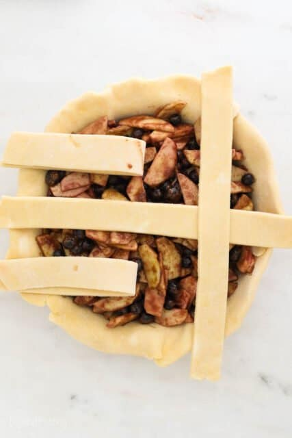 a pie plate filling with pie filling and 4 strips of dough laying across