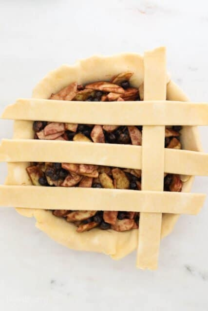 a pie plate filling with pie filling and 4 strips of dough laying across to build a lattice crust