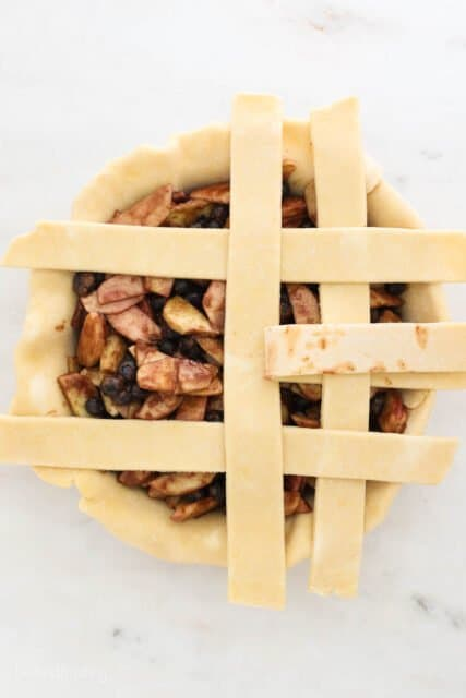 a pie plate filling with pie filling and 5 strips of dough laying across, one folded back