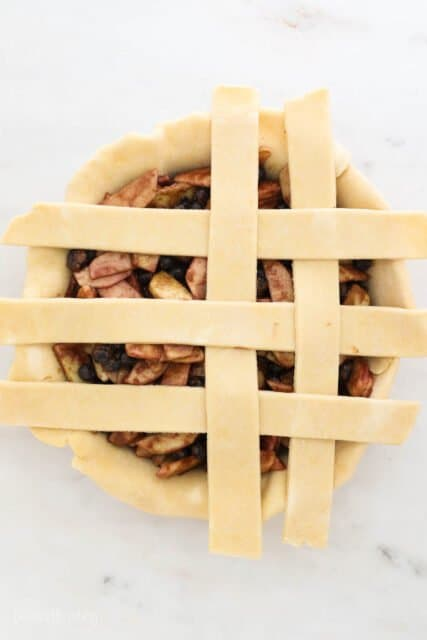 a pie plate filling with pie filling and 5 strips of dough laying across showing the process to build a lattice crust
