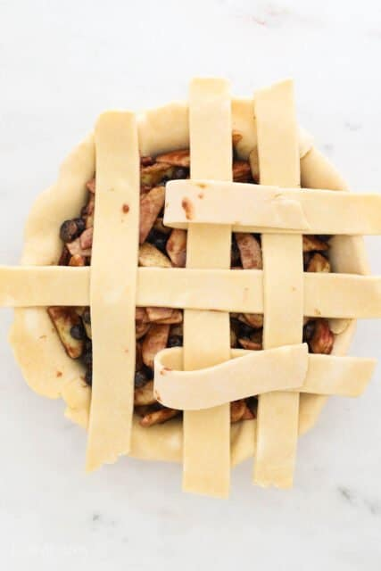 a pie plate filling with pie filling and 6 strips of dough laying across, two folded back