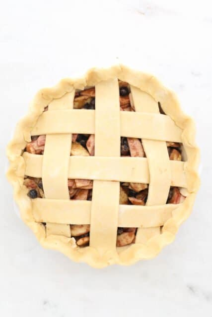 an unbaked pie with a lattice top crust
