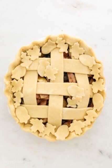 an unbaked pie with a lattice top crust and cutout pie crust leaf and acorn shapes laid on top