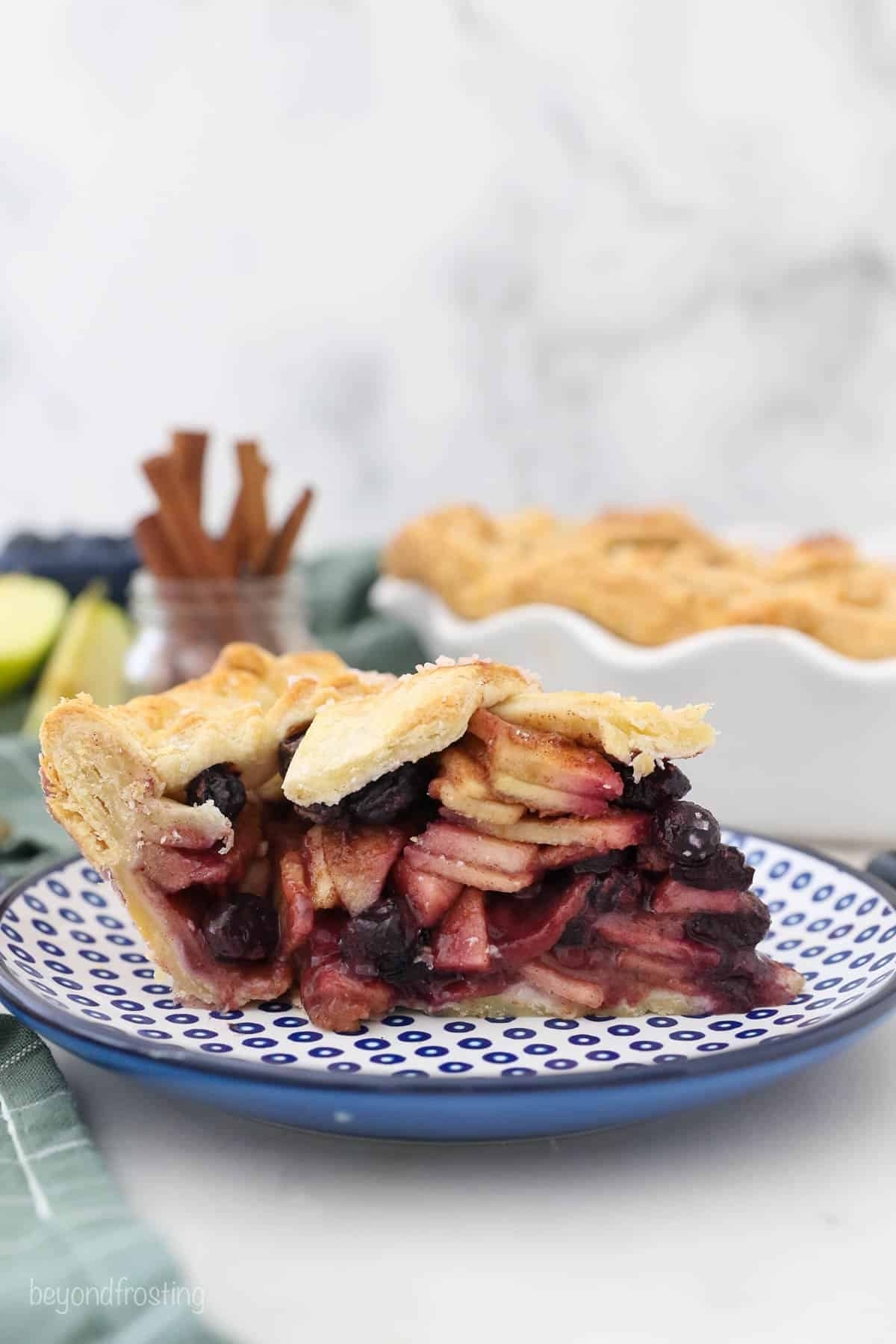 A side view of slice of apple and blueberry filled pie on a blue polka dot plate