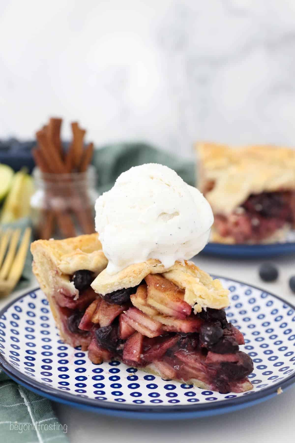 a slice of apple and blueberry pie with a scoop of vanilla ice cream on top