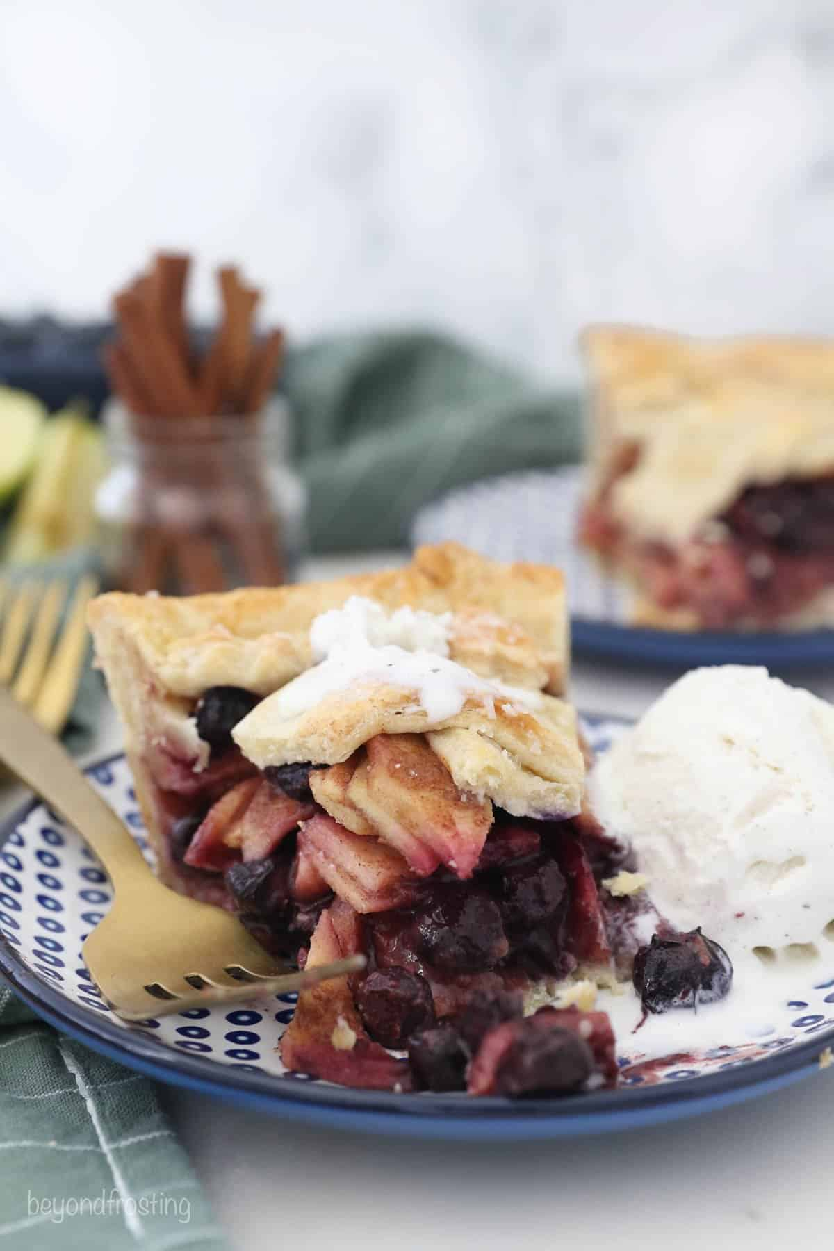 A half eaten slice of apple pie with blueberries and ice cream