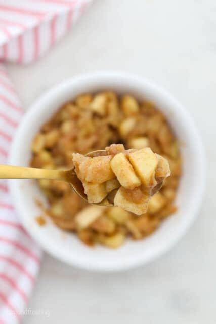 spoonful of apple pie filling held over bowl