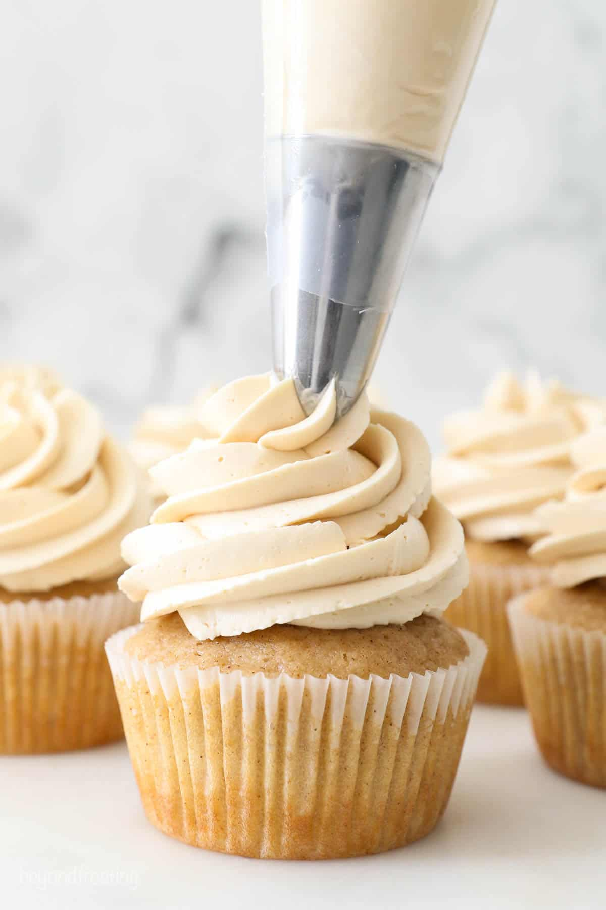 apple pie cupcakes being frosted