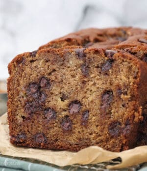Sliced banana bread with chocolate chips on a piece of brown parchment paper