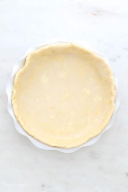 a gluten-free pie crust in a white pie dish