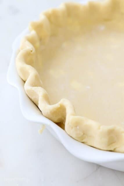 A close-up shot of the crimped edges of a homemade gluten free pie crust in a white pie dish