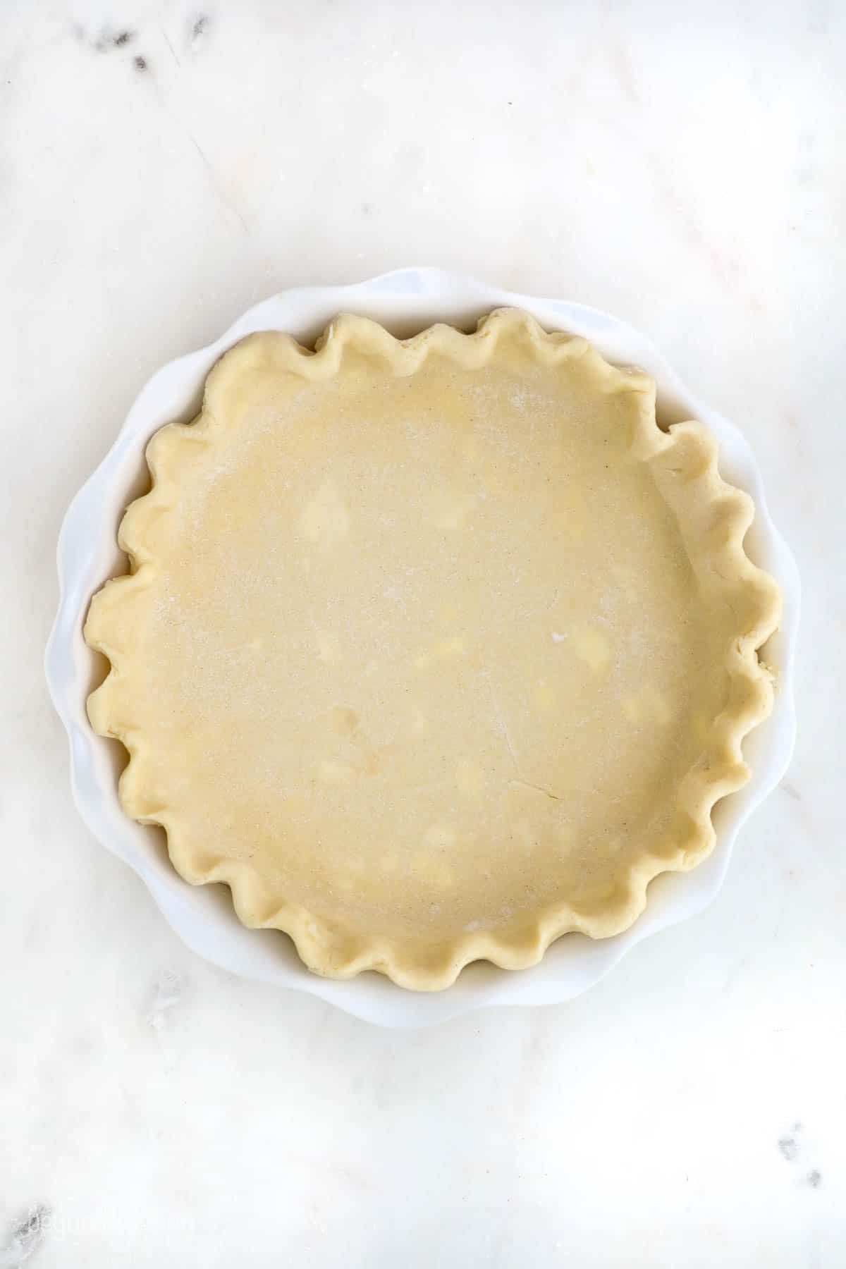 An unbaked pie crust with crimped edges in a white pie dish
