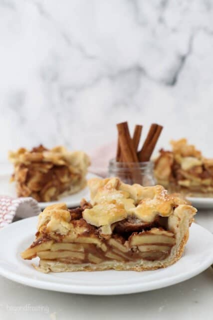 A slice of apple pie on a white plate, with additional slices blurred out in the background