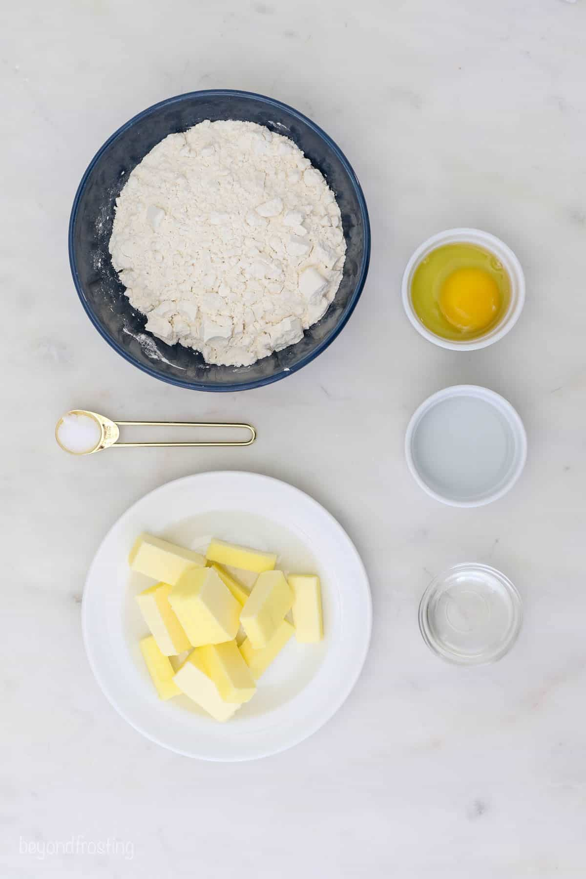 A bowl of flour, a plate of cold butter, a cracked egg in a dish and the rest of the dough ingredients arranged on a countertop