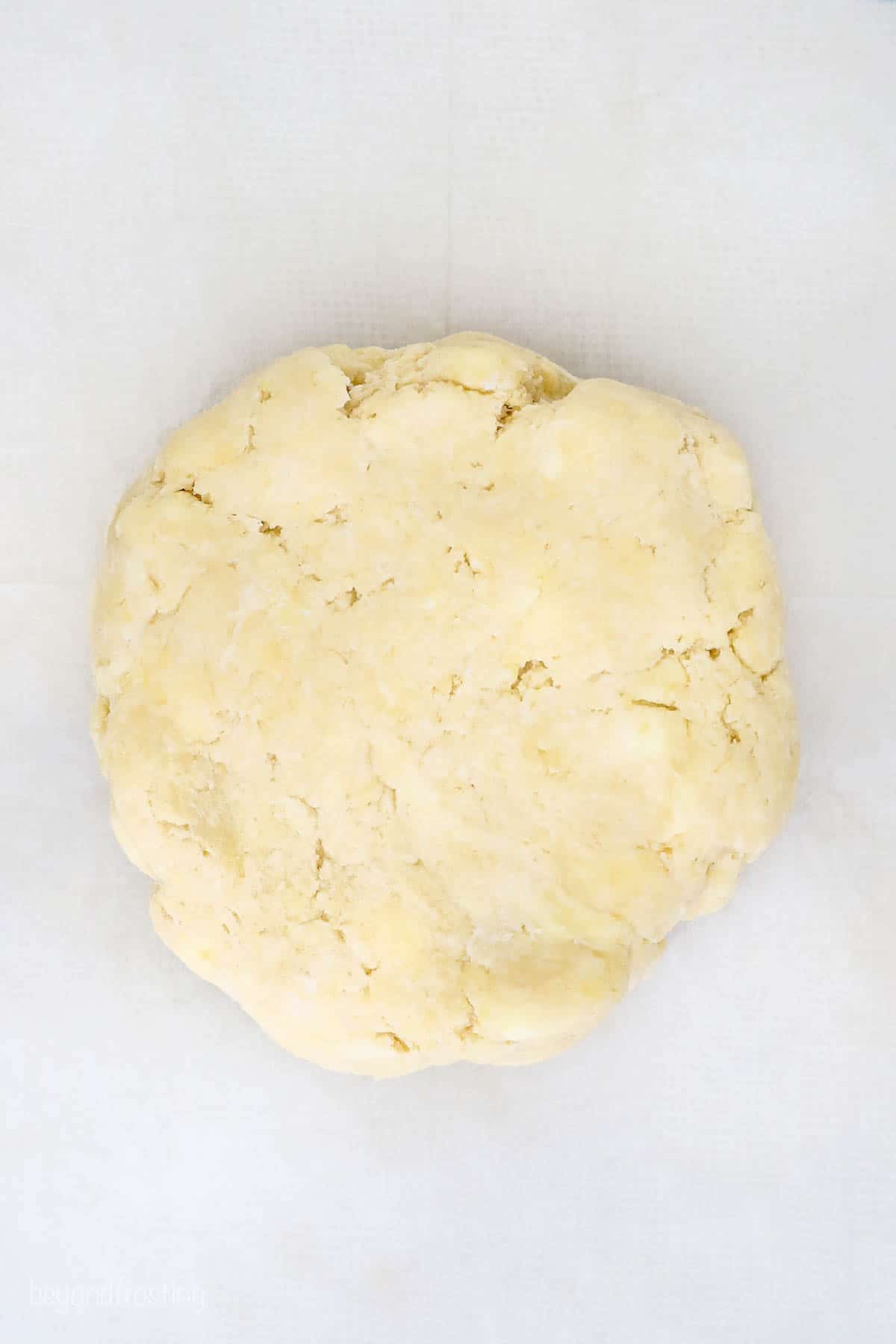 A disc of homemade butter pie dough on top of a smooth white surface