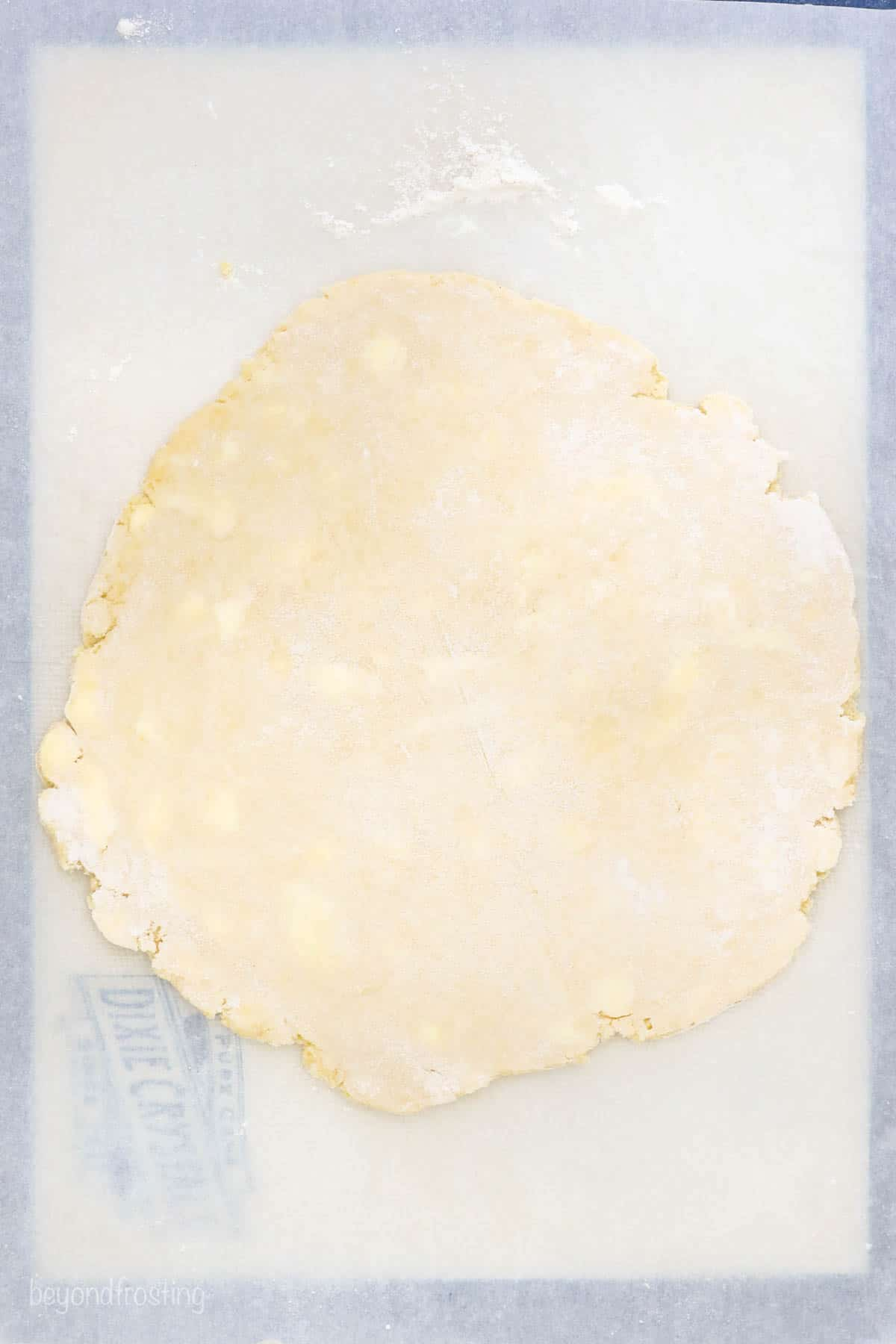 Rolled out pie dough on a piece of floured parchment paper with a silicone mat beneath it