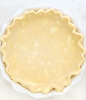An unbaked pie crust with crimped edges in a white pie plate
